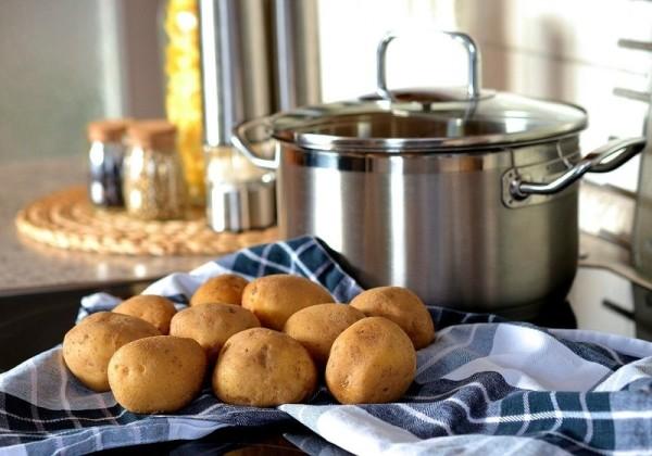 調理台の上にあるジャガイモとステンレスの鍋
