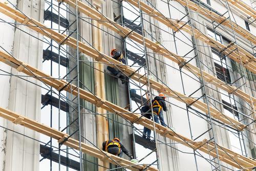 大規模修繕中のマンション。外壁が足場で覆われ、窓の外を作業員が行き来する