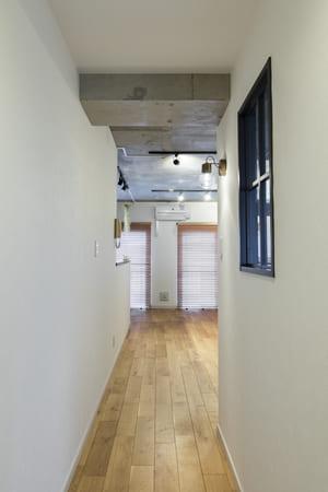 玄関リフォーム・インテリアコーディネートのポイント4。玄関ホールと居室の間仕切りに室内窓を設置することで、外窓のないマンションの玄関でも自然光が取り入れやすくなる。