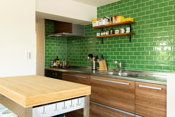 事例:https://hikarinobe.com/constructioncase/case_0060/より。キッチンの壁一面にグリーンのタイルを設えた。