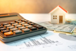 Real estate or property development. Construction business investment concept. Home mortgage loan rate. House model on international banknotes with calculator on the table.