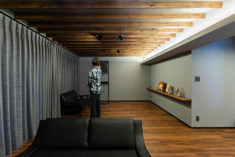 壁全面をグレーで統一し、間接照明をふんだんに用いたダーツバーのような趣きのリビング
