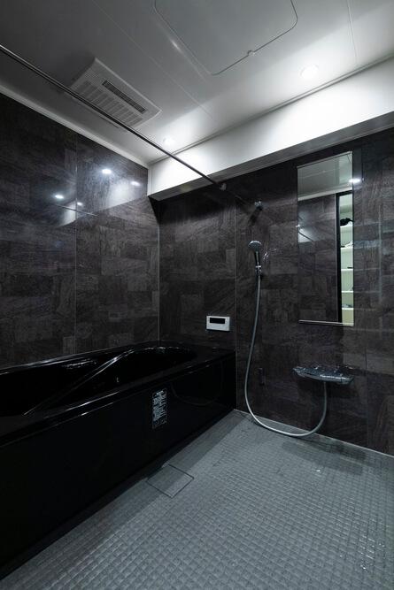 漆黒の浴槽が石造りの露天風呂を思わせる、マンションながら戸建並みに広いバスルーム