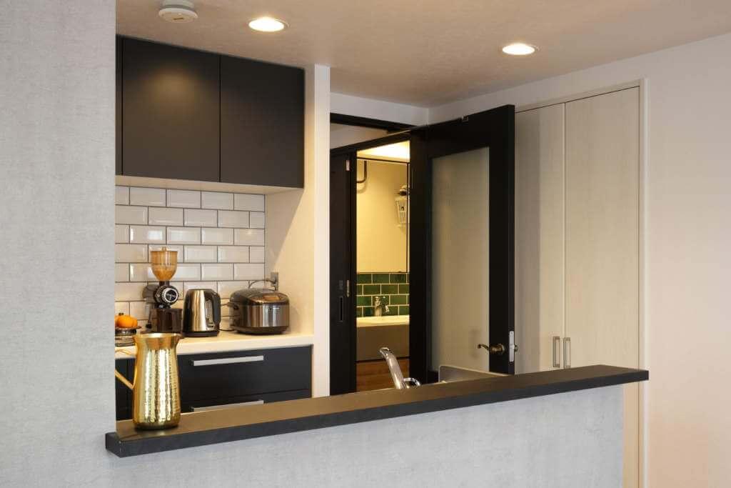 キッチンの白いサブウェイタイルと、洗面の深緑色のタイルがマッチしている様子