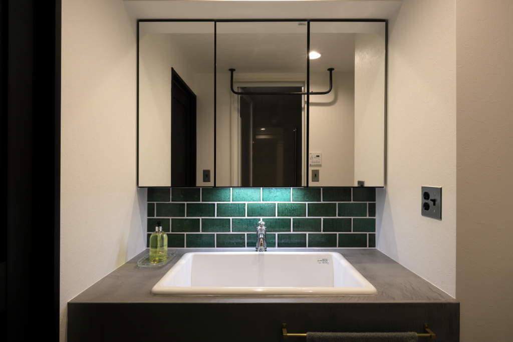 緑のタイルを映し出すセンサー照明を取り付けたご主人こだわりの造作洗面台
